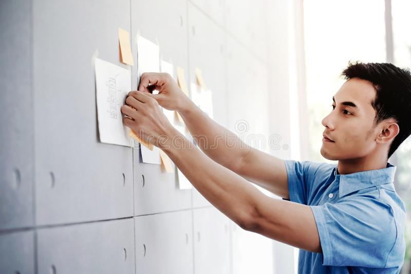 Young Asian Businessman Working in Office Meeting Room. Man Analyzing Data Plans and Project. Concentrate on Document Note on Board stock image