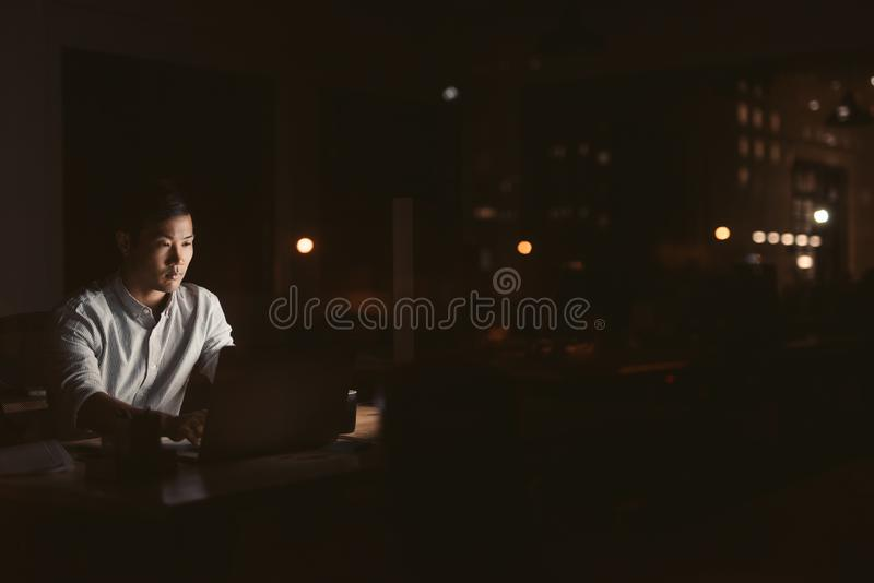 Young Asian businessman working late at night in an office royalty free stock images