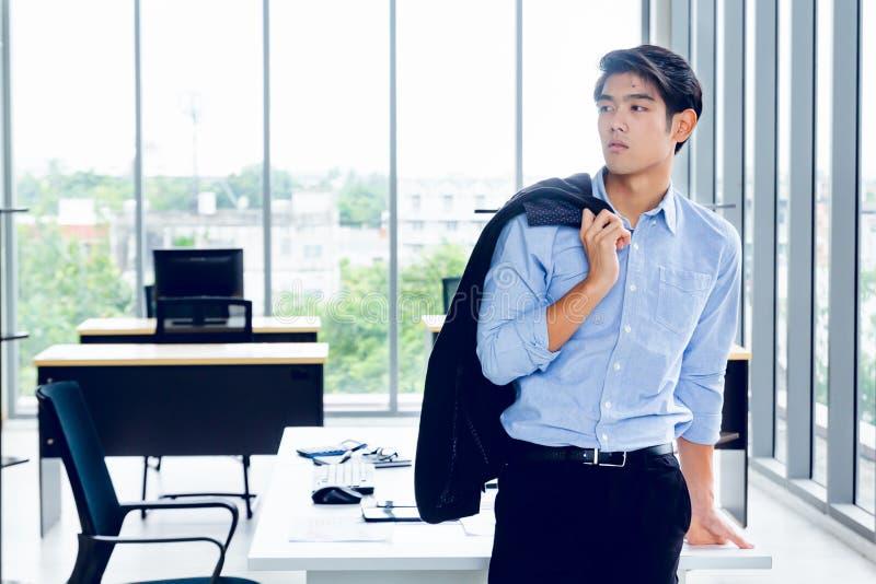 Young Asian Businessperson se tient debout dans des poses intelligentes et sourit dans un espace de co-travail décoré dans un sty image stock