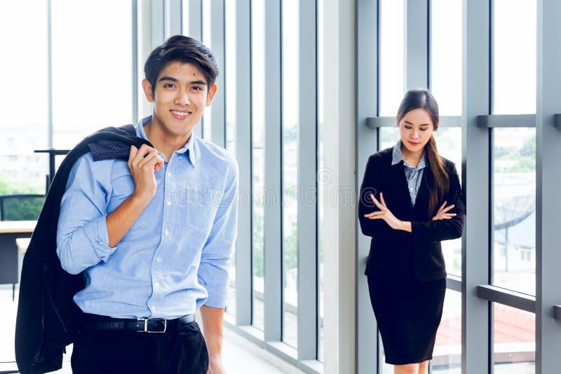 Young Asian Businessperson steht für intelligente Posen und Lächeln im Arbeitsraum, der im modernen Bürostil für die Gründung von stockbild