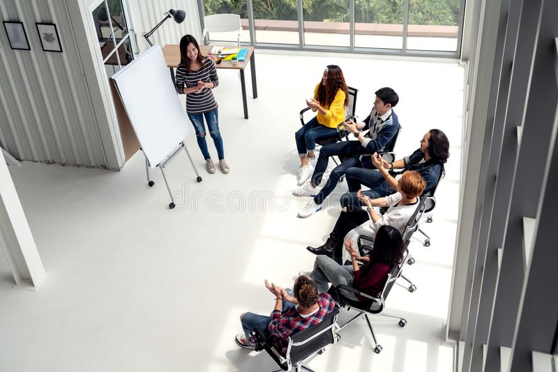 Young asian businesswoman explain idea to group of creative diverse team at modern office. Wide top view of manager standing against multiethnic people stock image