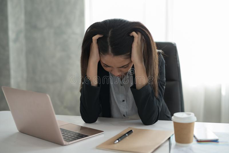 Young asian businesswoman feel stressed/worry/headache/disappoint during working while sit at office royalty free stock photos