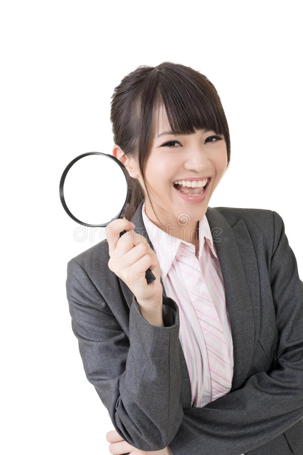 Young asian businesswoman holding magnifying glass royalty free stock photography