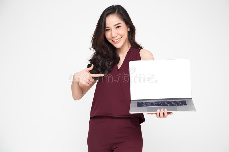 Young Asian businesswoman showing a laptop over white background and pointing finger to white screen of notebook with copy space stock images