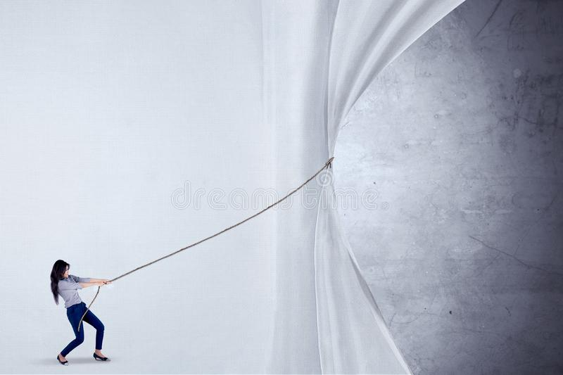Businesswoman pulling curtain with rope. Young Asian businesswoman using a rope to pull a big curtain or empty banner for copyspace royalty free stock photo