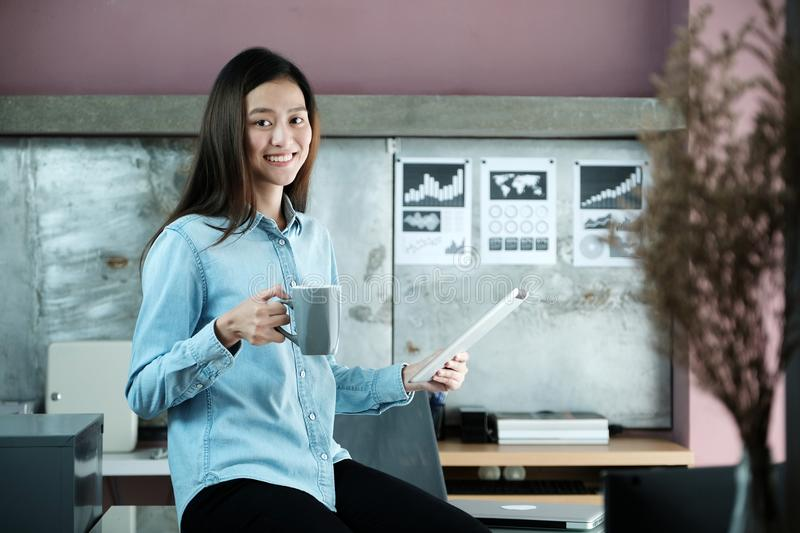 Young asian businesswoman using tablet and holding coffee cup wi royalty free stock photo