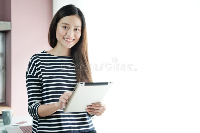 Young asian businesswoman using tablet with smiling face, positive emotion, at office, casual office life concept stock photos