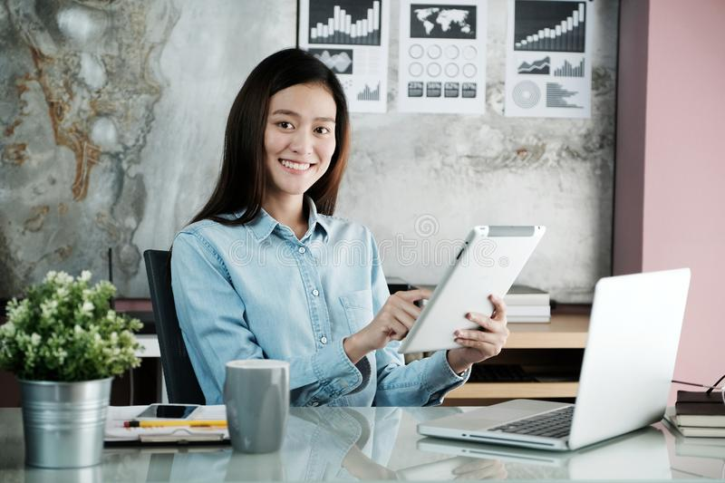 Young asian businesswoman using tablet with smiling face, positive emotion, at office, casual office life concept royalty free stock image