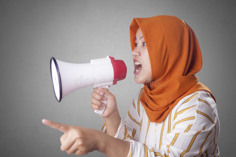 Young Businesswoman Angry, Screaming Using Megaphone. Young Asian businesswoman wearing suit and hijab screaming on megaphone with an angry expression. Close up stock photos