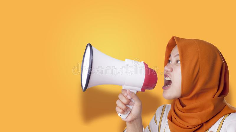 Young Businesswoman Angry, Screaming Using Megaphone. Young Asian businesswoman wearing suit and hijab screaming on megaphone with an angry expression. Close up stock photography