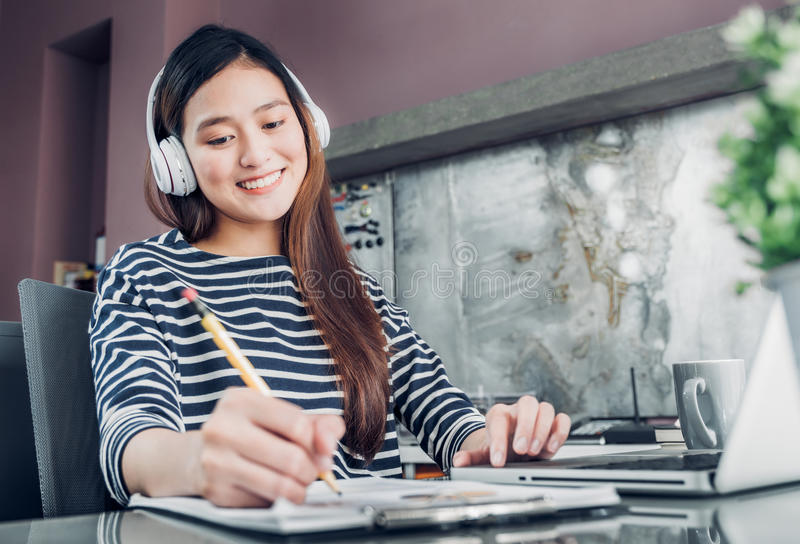 Young asian casual businesswoman listening music and writing rep stock images