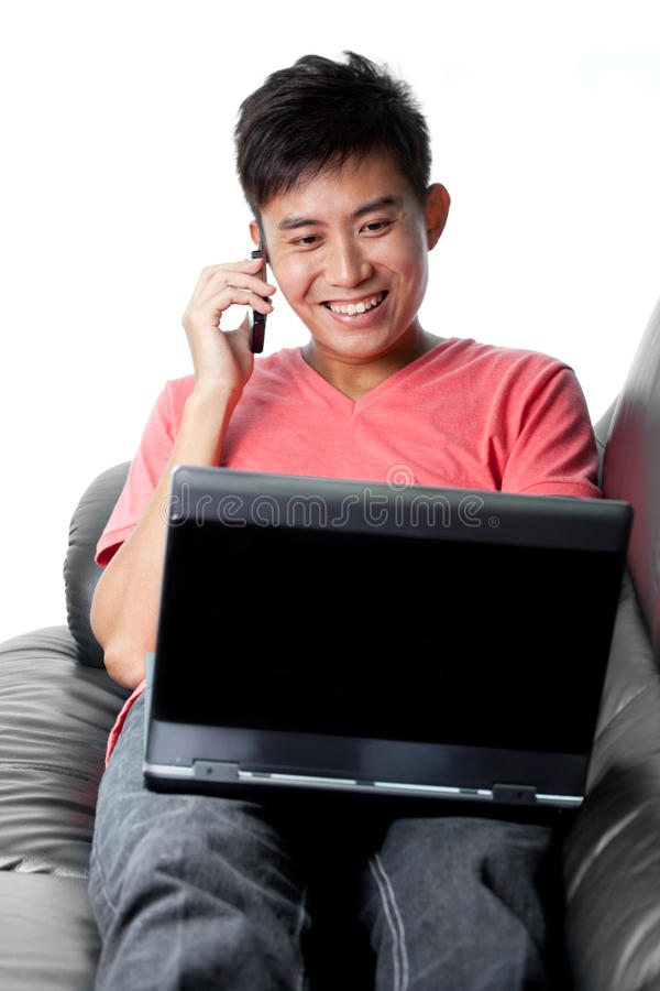 Young Asian Chinese surfs net and chats on phone royalty free stock photo