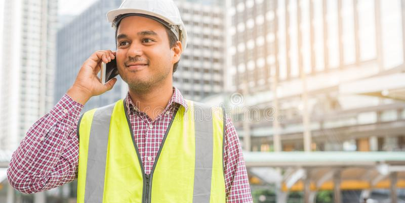 Young asian civil engineering talking on phone at construction building background. royalty free stock photo