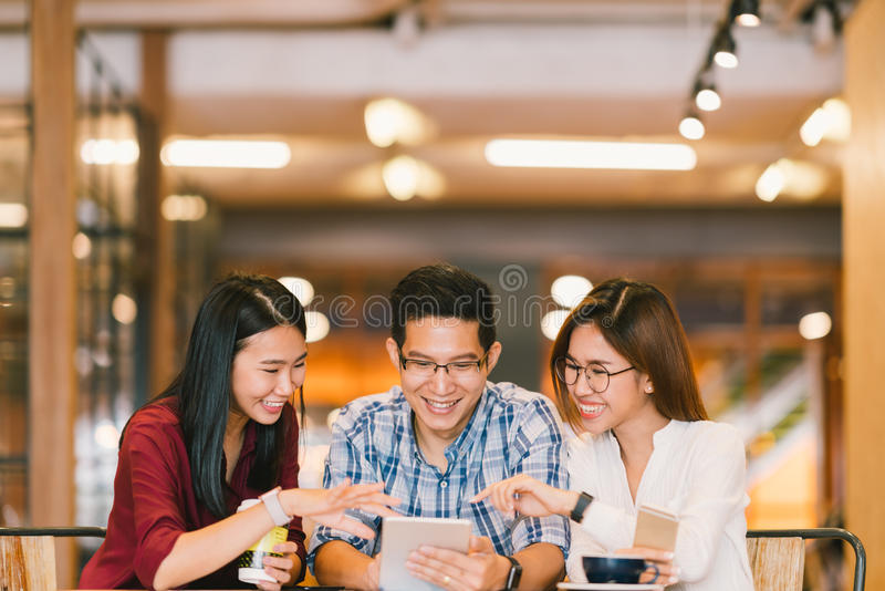 Young Asian college students or coworkers using digital tablet together at coffee shop, diverse group. Casual business, freelance. Work at cafe, social meeting royalty free stock image