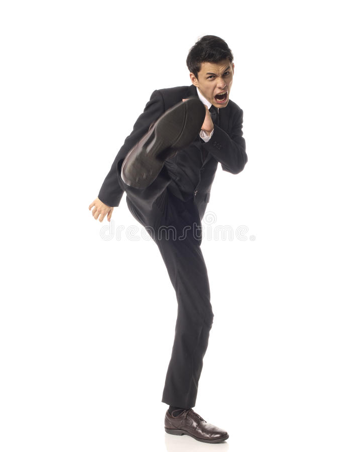 Young Asian Corporate Man kicking angrily. Over White Background stock photography