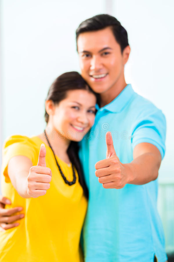 Download Young Asian Couple In Apartment With Thumbs Up Stock Image - Image: 38145789