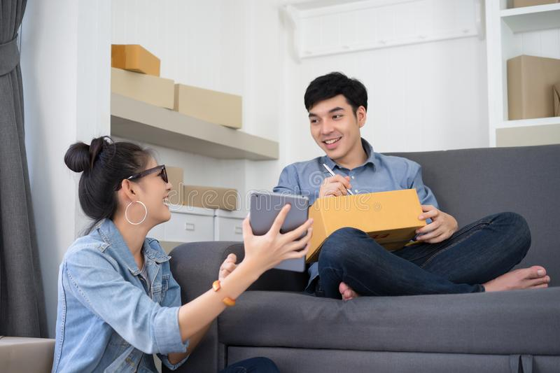 Young Asian couple casual working small business online packing royalty free stock images