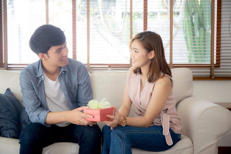 Young asian couple celebrate birthday together, asia man giving gift box present to woman for surprise at living room stock image