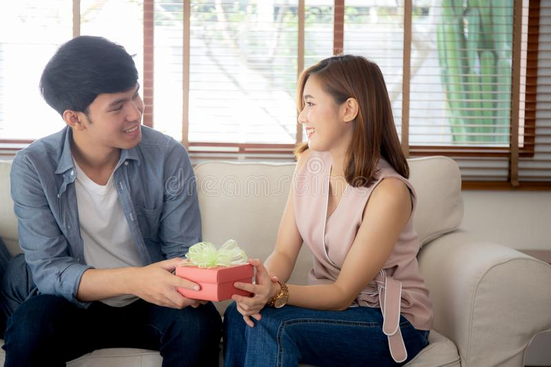 Young asian couple celebrate birthday together, asia man giving gift box present to woman for surprise at living room royalty free stock image