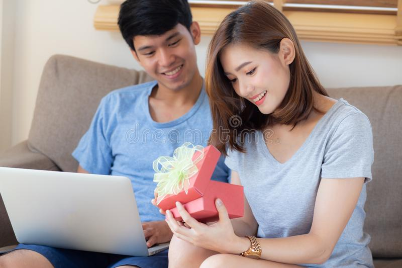 Young asian couple celebrate birthday together, asia man giving gift box present to woman for surprise at living room royalty free stock photos