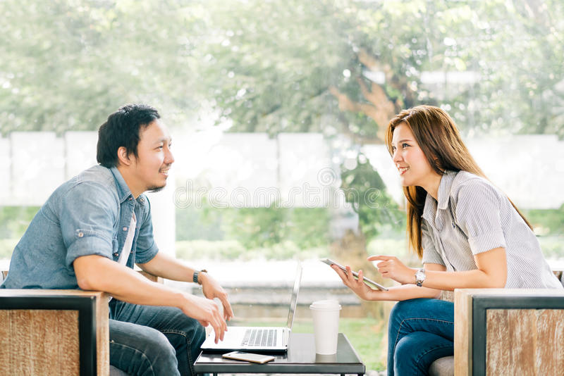 Young Asian couple or coworker talking at coffee shop or modern office. Garden background. With laptop notebook, smartphone and digital tablet. Modern stock photography