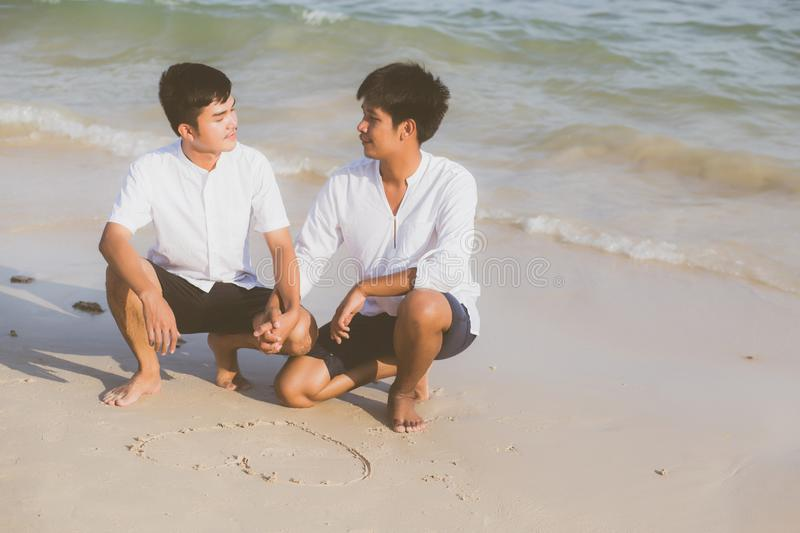 Young asian couple gay smiling romantic drawing heart shape together on sand in vacation. Homosexual happy and fun with love sitting on sand at the beach in royalty free stock photos