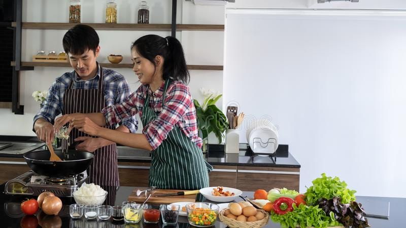 Young Asian couple are happy to cook together, And help to cook food in the morning. Young Asian couple are happy to cook together, two families are helping each royalty free stock image