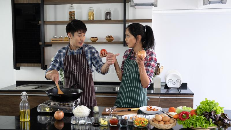 Young Asian couple are happy to cook together, two families are helping each other prepare to cook in the kitchen royalty free stock image