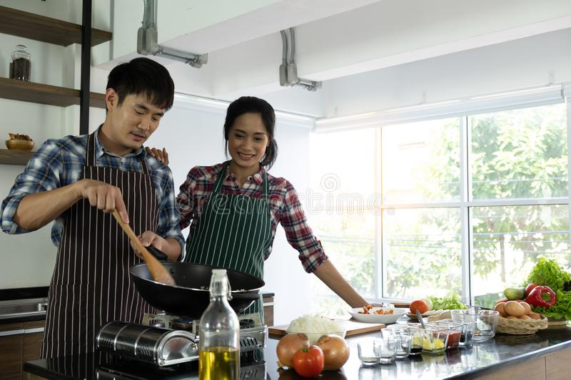 Young Asian couple are happy to cook together. Two families are helping each other prepare to cook in the kitchen royalty free stock photos