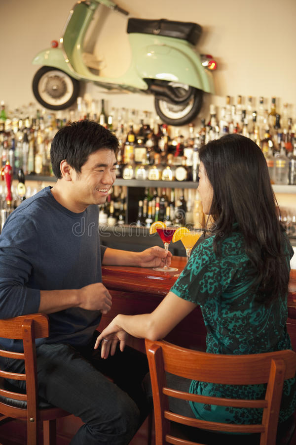 Young Asian couple having drinks stock image