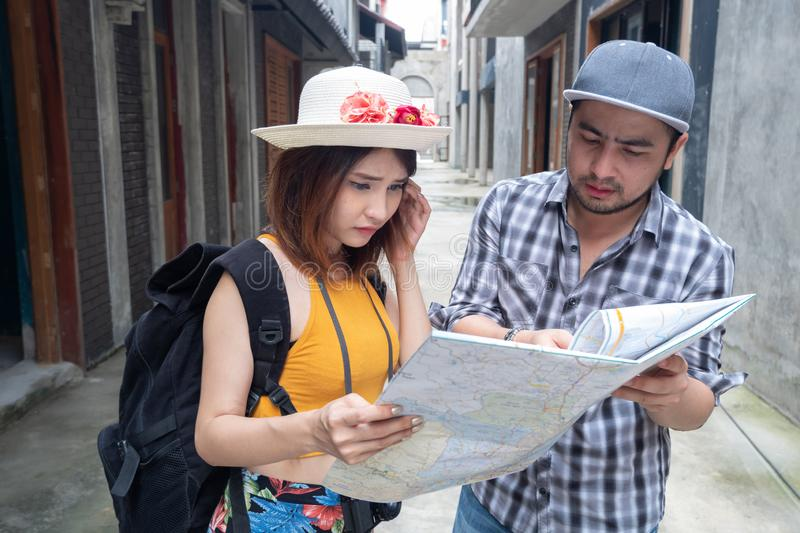 Young Asian couple holding map looking direction on honeymoon vacation..Tourist people on summer lost together on holiday trip. stock image