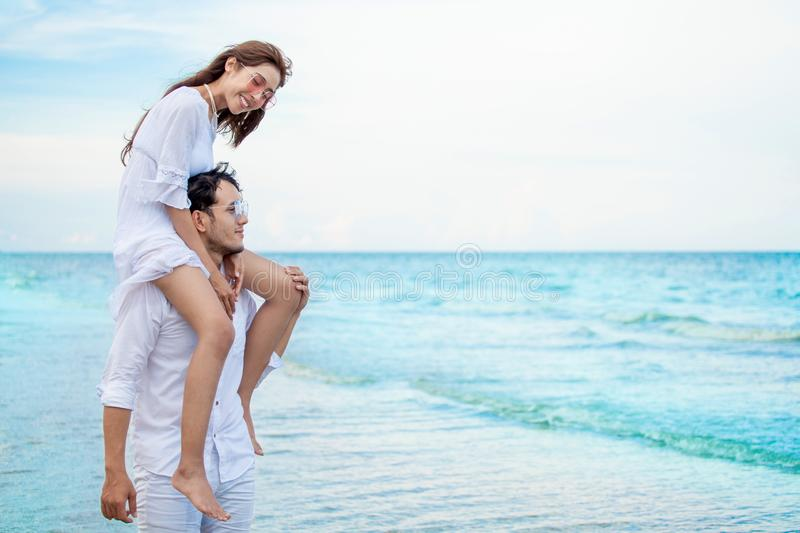 Young asian couple in love honeymoon at sea beach on blue sky. boyfriend piggy back ride to girlfriend . happy smiling wedding royalty free stock photo