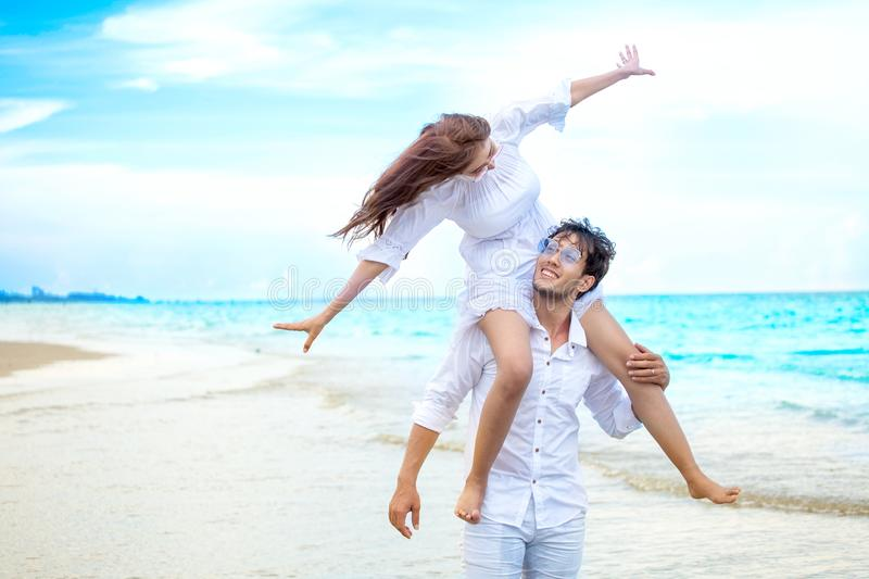 Young asian couple in love honeymoon at sea beach on blue sky. husband giving piggy back ride to wife . happy smiling wedding royalty free stock photography