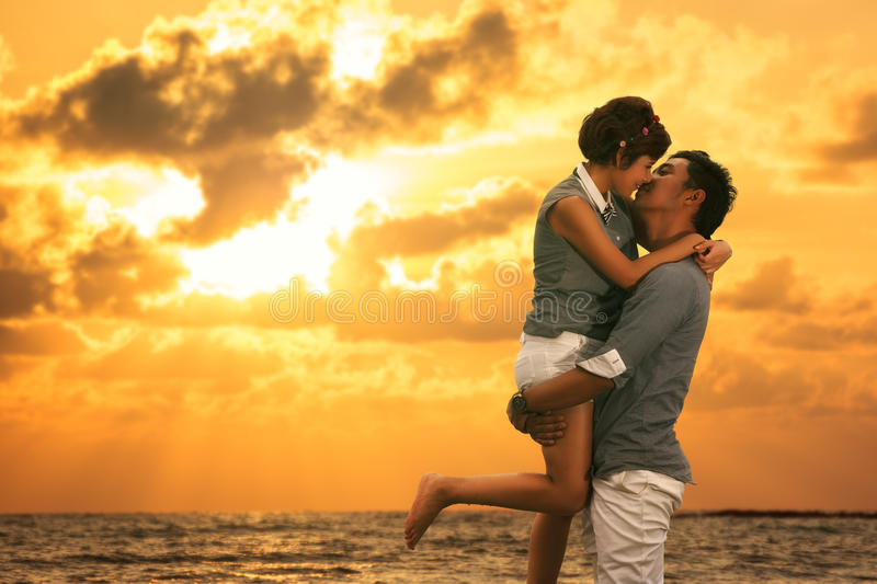 Young asian couple in love staying and kissing on the beach. On sunset royalty free stock photo