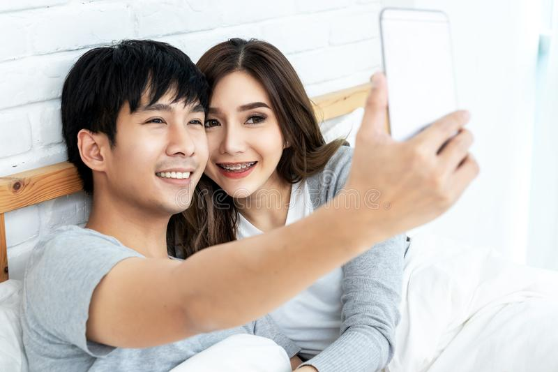 Young asian couple lying on bed and taking selfie by smartphone. Asian lovers take a photo with toothy smile. Happy lover hug each stock photo