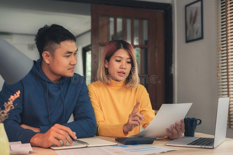 Young asian couple managing finances, reviewing their bank accounts using laptop computer and calculator at modern home. royalty free stock images