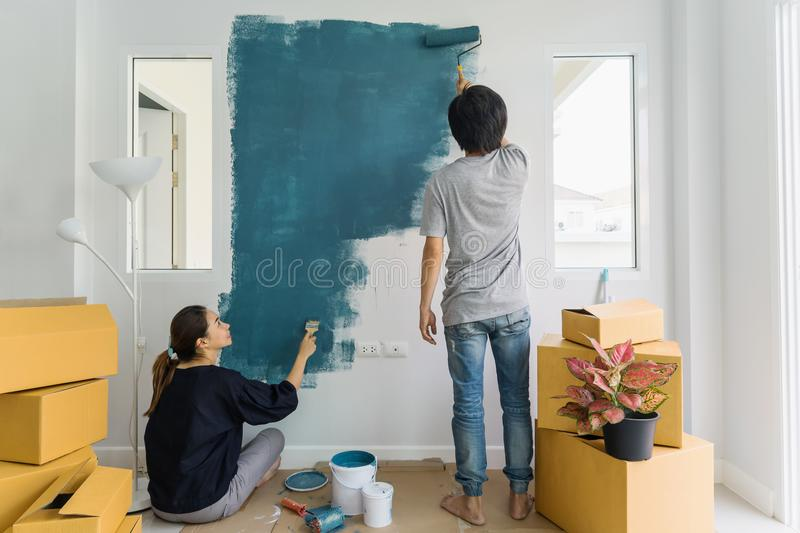 Young asian couple painting interior wall with paint roller in n. Ew house royalty free stock image