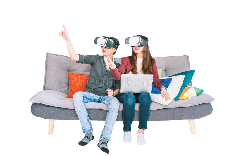 Young Asian couple playing VR virtual reality gadget, sitting on sofa together, isolated on white background. Modern gaming tech stock photo