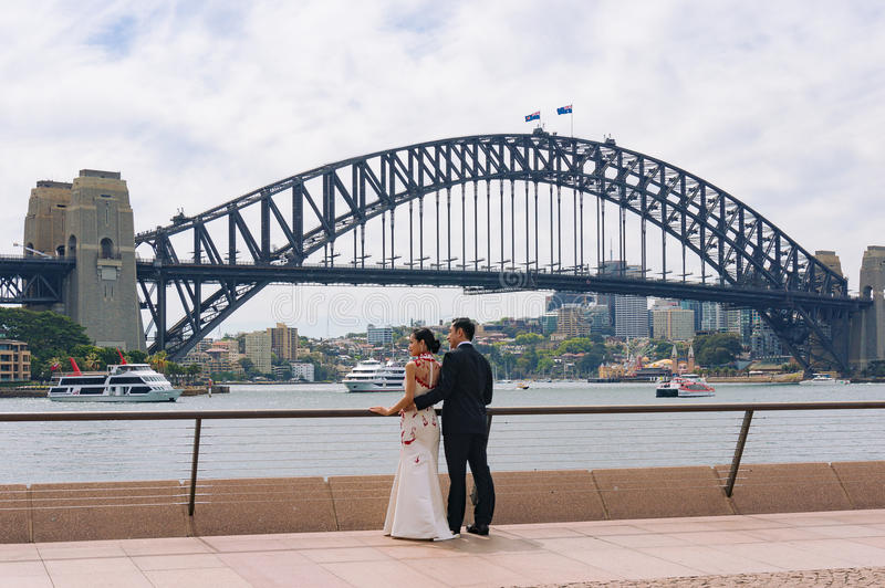 Young Asian couple posing against Sydney Harbour Bridge on background stock photo
