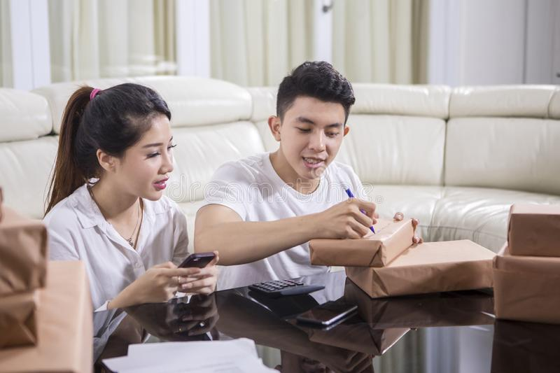Asian couple writing the address on a package royalty free stock photography