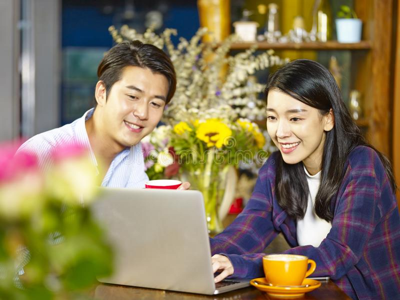 Young asian couple relaxing in coffee shop. Happy young asian couple using laptop computer in coffee shop royalty free stock photography
