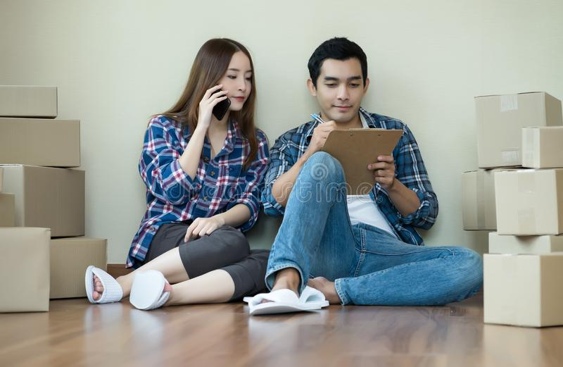 Young Asian couple sitting on floor check product order at home royalty free stock photography