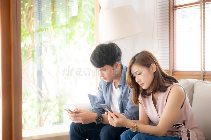 Young asian couple sitting on sofa with problem about relationship because addicts social network media together stock images