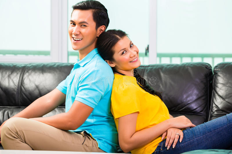 Young Asian couple on sofa or couch. Young Asian handsome couple having long-term relationship sitting on sofa or couch royalty free stock photos