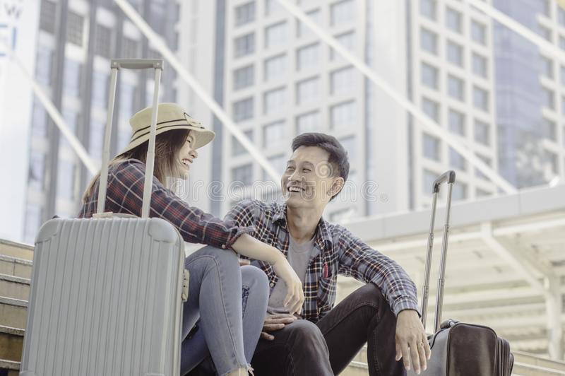 Young Asian Couple of travelers Smiling happily while sitting wi royalty free stock photography