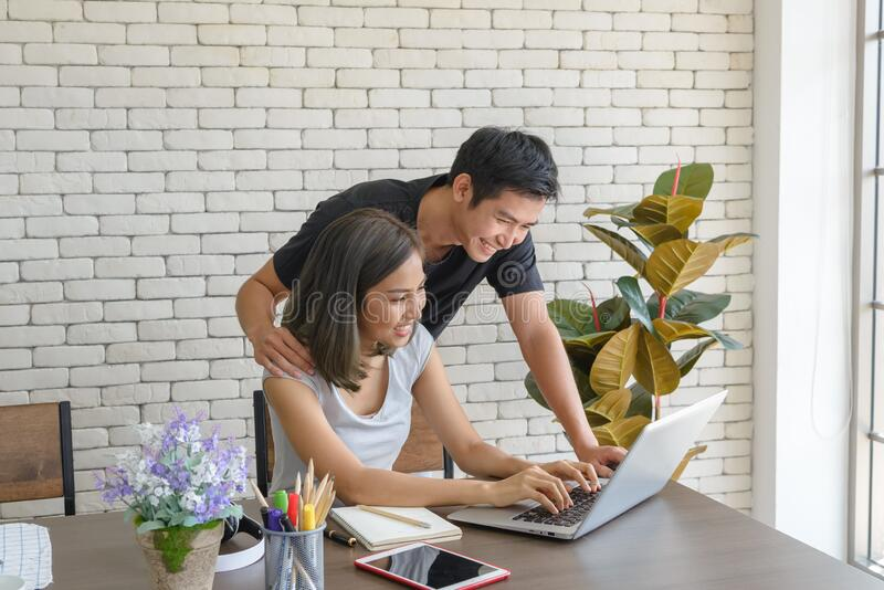 Couple wear casual clothing relaxing while sitting at big wooden table in modern kitchen and working with computer laptop at home. stock image