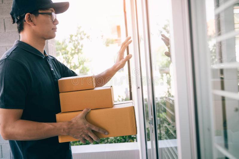 Young asian courier is using the hand of the knock at the door to deliver the goods royalty free stock photos