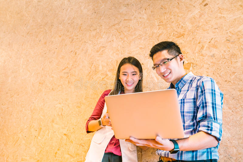 Asian coworker or college student team using laptop computer together at office or campus. Happy casual business talk. Young Asian coworker or college student stock photography