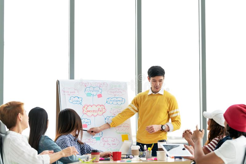 Young asian creative businessman standing and making presentation at modern office happy talking and brainstorming with team by stock photo