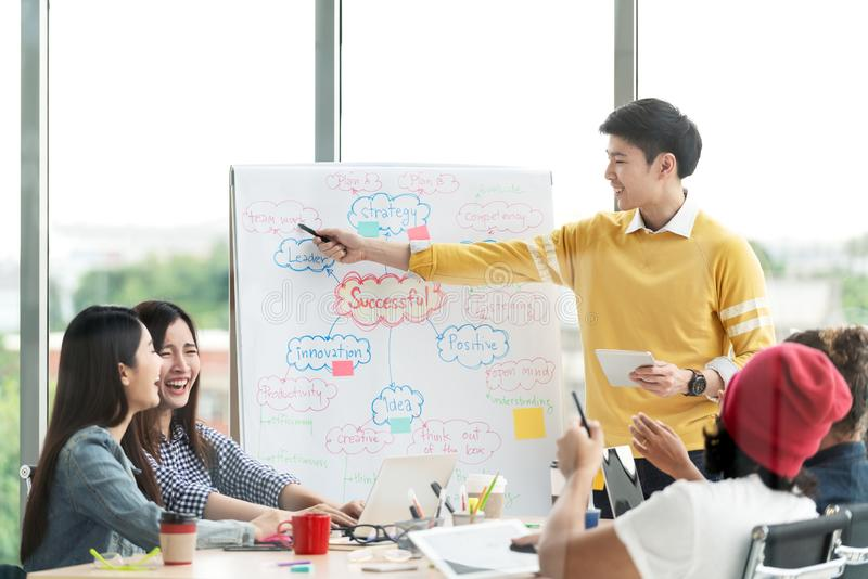 Young asian creative businessman standing and making presentation at modern office happy talking and brainstorming with team by stock photography